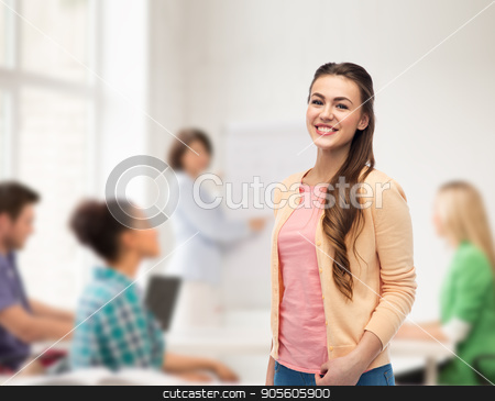 happy smiling young woman in cardigan stock photo, education, high school and people concept - happy smiling young student woman over classroom background by Syda Productions