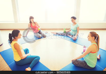 happy pregnant women sitting on mats in gym stock photo, pregnancy, sport, fitness, people and healthy lifestyle concept - group of happy pregnant women with water bottles sitting on mats and talking in gym by Syda Productions