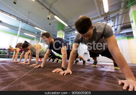 group of people exercising in gym stock photo, fitness, sport, exercising, training and healthy lifestyle concept - group of people doing straight arm plank in gym by Syda Productions