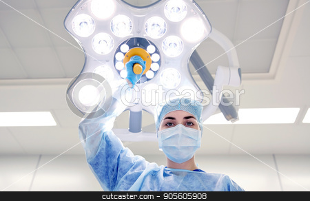 surgeon in operating room at hospital stock photo, surgery, medicine and people concept - surgeon in mask adjusting lamp in operating room at hospital by Syda Productions