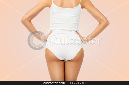 close up of woman body in white underwear stock photo, beauty, people and bodycare concept - close up of beautiful young woman body in white underwear from back over beige background by Syda Productions