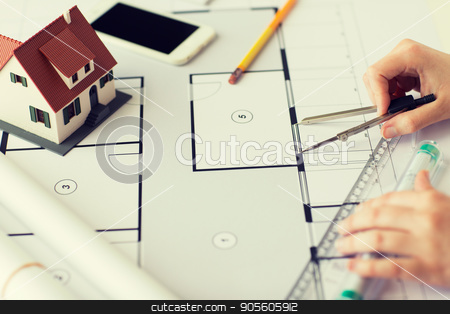 close up of hands with compass measuring blueprint stock photo, business, architecture, building, construction and people concept - close up of architect hands with compass and ruler measuring living house blueprint by Syda Productions