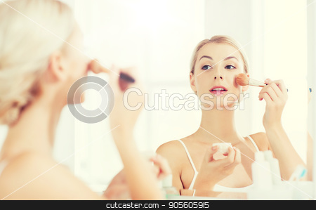 woman with makeup brush and powder at bathroom stock photo, beauty, make up, cosmetics, morning and people concept - smiling young woman makeup brush and powder foundation looking to mirror at home bathroom by Syda Productions