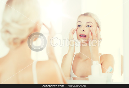 happy woman applying cream to face at bathroom stock photo, beauty, skin care and people concept - smiling young woman applying cream to face and looking to mirror at home bathroom by Syda Productions
