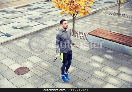 man exercising with jump-rope outdoors stock photo, fitness, sport, people, exercising and lifestyle concept - man skipping with jump rope outdoors by Syda Productions