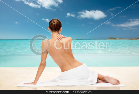 beautiful woman in towel with bare top on beach stock photo, beauty, people and bodycare concept - beautiful young woman in white towel with bare top over exotic tropical beach background by Syda Productions