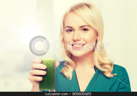 smiling woman drinking juice or smoothie at home stock photo, healthy eating, vegetarian food, diet, detox and people concept - smiling young woman drinking green vegetable juice or smoothie from glass at home by Syda Productions