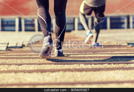 close up of couple running downstairs on stadium stock photo, fitness, sport, exercising and lifestyle concept - close up of couple running downstairs on stadium by Syda Productions