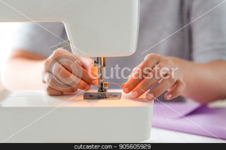tailor woman threading needle of sewing machine stock photo, people, needlework and tailoring concept - tailor woman threading needle of sewing machine at studio by Syda Productions