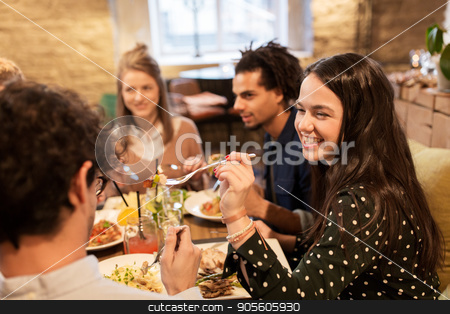 happy friends eating and drinking at restaurant stock photo, leisure, food, drinks, people and holidays concept - happy friends eating and drinking at restaurant by Syda Productions