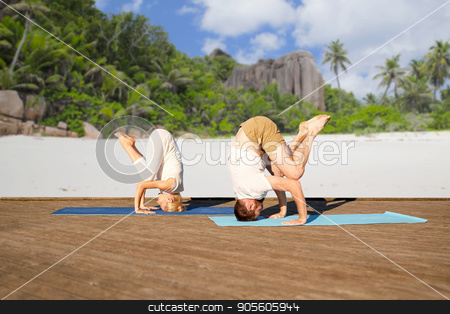 couple making yoga over tropical beach stock photo, fitness, sport, yoga, people and healthy lifestyle concept - couple making headstand outdoors over tropical beach background by Syda Productions