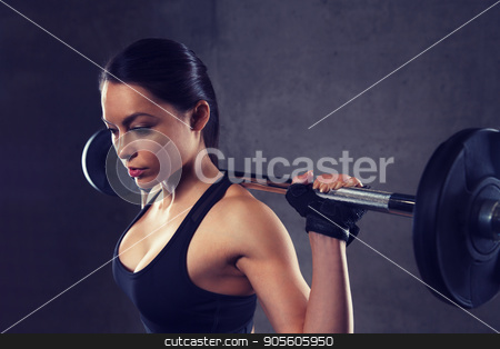 young woman flexing muscles with barbell in gym stock photo, sport, fitness, bodybuilding, weightlifting and people concept - young woman with barbell flexing muscles in gym by Syda Productions