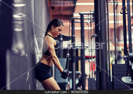 woman flexing arm muscles on cable machine in gym stock photo, sport, fitness, bodybuilding, lifestyle and people concept - woman flexing arm muscles on cable machine in gym by Syda Productions