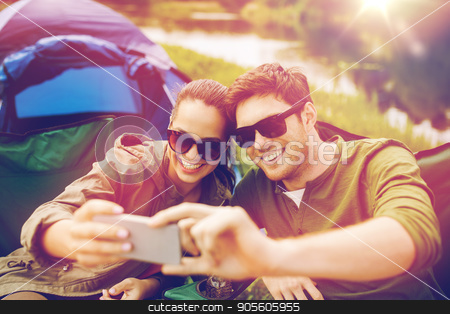 couple of travelers taking selfie by smartphone stock photo, travel, hiking, technology, tourism and people concept - smiling couple of travelers taking selfie by smartphone at camping by Syda Productions