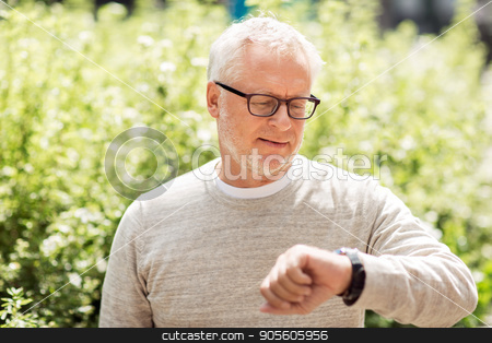 senior man checking time on his wristwatch stock photo, punctuality and people concept - senior man checking time on wristwatch or smart watch on his hand outdoors by Syda Productions