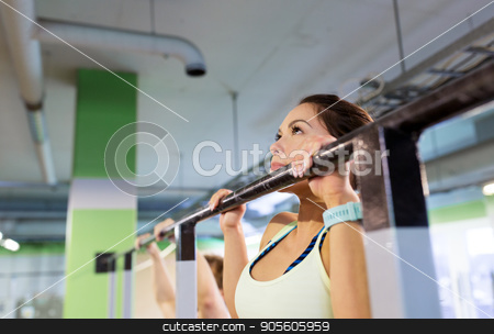 woman exercising and doing pull-ups in gym stock photo, sport, fitness and people concept - woman exercising and doing pull-ups at horizontal bar in gym by Syda Productions