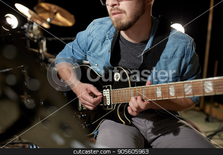 man playing guitar at studio rehearsal stock photo, music, people, musical instruments and entertainment concept - male guitarist playing electric guitar at studio rehearsal by Syda Productions