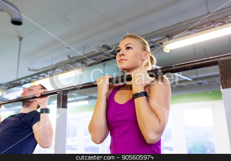 couple doing pull-ups at horizontal bar in gym stock photo, sport, fitness and training concept - man and woman doing pull-ups at horizontal bar in gym by Syda Productions