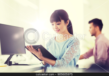 happy creative female office worker with tablet pc stock photo, business, startup and people concept - happy asian businesswoman or creative female office worker with tablet pc computer by Syda Productions