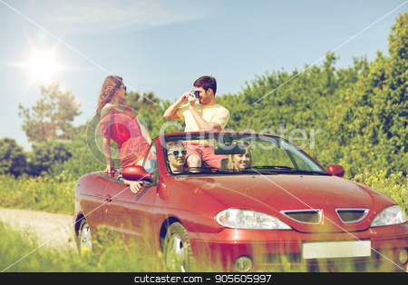 happy friends with camera driving in cabriolet car stock photo, leisure, road trip, travel, summer holidays and people concept - happy friends driving in cabriolet car and taking picture by film camera by Syda Productions
