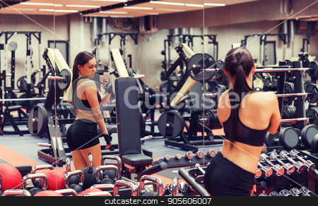 woman with smartphone taking mirror selfie in gym stock photo, sport, fitness, lifestyle, technology and people concept - young woman with smartphone taking mirror selfie in gym by Syda Productions