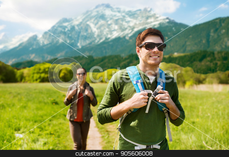 happy couple with backpacks hiking outdoors stock photo, travel, tourism and people concept - happy couple with backpacks walking along country road over mountains background by Syda Productions