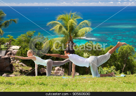 happy couple making yoga exercises outdoors stock photo, fitness, sport, relax and people concept - happy couple making yoga in balancing table pose outdoors over natural background by Syda Productions