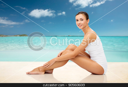 beautiful woman touching her legs on summer beach stock photo, beauty, people and bodycare concept - beautiful woman in white underwear touching her smooth bare legs over exotic tropical beach background by Syda Productions