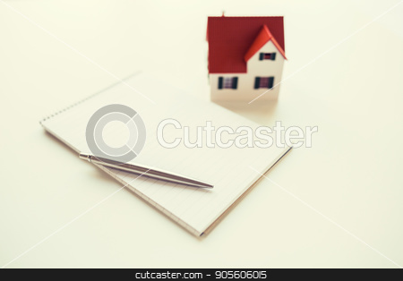 close up of house model, notebook and pencil stock photo, building, mortgage, real estate and property concept - close up of house model, notebook and pencil by Syda Productions