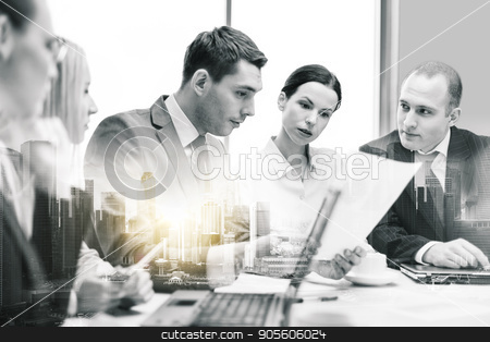 business team with laptop and papers at office stock photo, business, teamwork and people concept - serious team with laptop computer and papers having discussion at office over city buildings and double exposure effect by Syda Productions