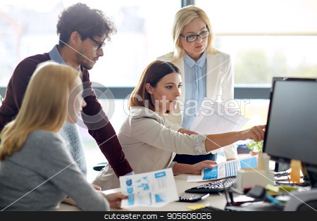 happy business team with computer in office stock photo, business, startup and people concept - happy creative team with papers and computer in office by Syda Productions