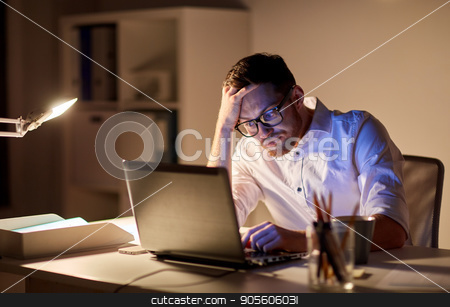 businessman with laptop thinking at night office stock photo, business, overwork, people, deadline and technology concept - stressed businessman in glasses with laptop computer thinking at night office by Syda Productions