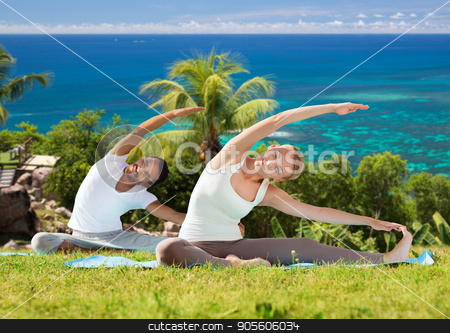 happy couple making yoga exercises outdoors stock photo, fitness, sport, relax and people concept - happy couple making yoga exercises sitting on mats outdoors over natural background by Syda Productions