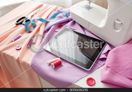 sewing machine, tablet pc, scissors and ruler stock photo, needlework, technology and tailoring concept - sewing machine with tablet pc computer, scissors, tape measure and fabric by Syda Productions
