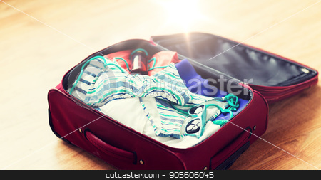 close up of travel bag with beach clothes stock photo, summer vacation, travel, tourism and objects concept - close up of travel bag with beach clothes, sunglasses and sunscreen by Syda Productions