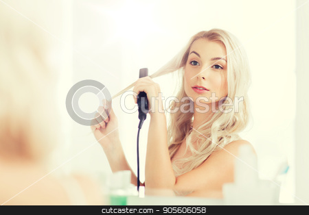 woman with styling iron doing her hair at bathroom stock photo, beauty, hairstyle, morning and people concept - smiling young woman with styling iron straightening her hair and looking to mirror at home bathroom by Syda Productions