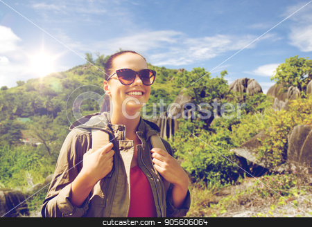 happy young woman with backpack traveling stock photo, travel, tourism and people concept - happy young woman in sunglasses with backpack over natural exotic island background by Syda Productions