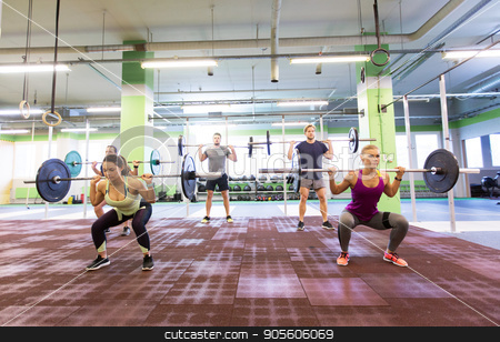 group of people training with barbells in gym stock photo, fitness, sport, training, exercising and lifestyle concept - group of people with barbells doing squats in gym by Syda Productions