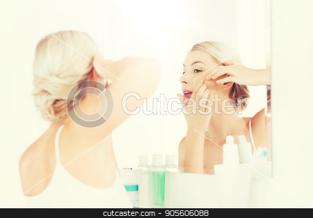 woman squeezing pimple at bathroom mirror stock photo, beauty, hygiene, skin problem and people concept - young woman looking to mirror and squeezing pimple at home bathroom by Syda Productions