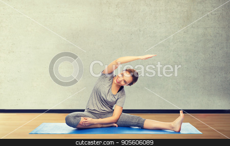 happy woman making yoga and stretching on mat stock photo, fitness, sport, people and healthy lifestyle concept - happy woman making yoga and stretching on mat over gym room background by Syda Productions