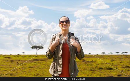 happy woman with backpack traveling in africa stock photo, travel, tourism and people concept - happy young woman in sunglasses with backpack over african savannah background by Syda Productions