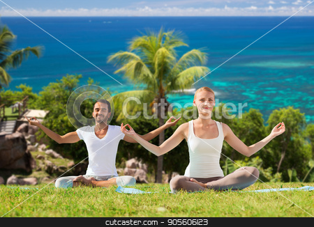 happy couple doing yoga and meditating outdoors stock photo, fitness, sport, meditation and people concept - happy couple doing yoga and meditating outdoors over natural background and sea by Syda Productions