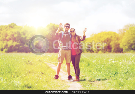 happy couple with backpacks hiking outdoors stock photo, travel, hiking, backpacking, tourism and people concept - happy couple with backpacks waving hands and walking along country road outdoors by Syda Productions