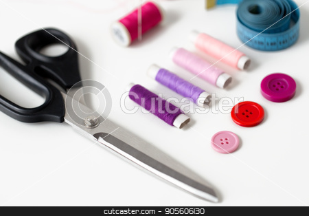 scissors, sewing buttons, threads and tape measure stock photo, needlework and tailoring concept - scissors, sewing buttons, spools of thread and tape measure by Syda Productions