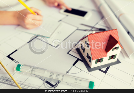 close up of living house model on blueprint stock photo, business, architecture, building, construction and people concept - close up of living house model on blueprint over architect hands by Syda Productions