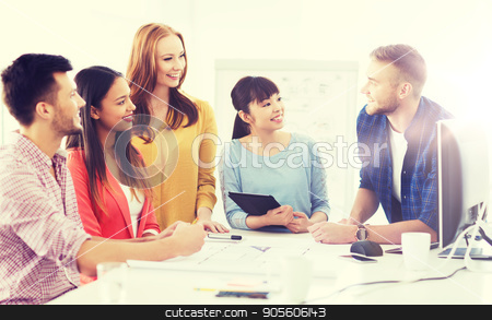 happy creative team or students working at office stock photo, business, startup, education and people concept - happy creative architect team or students with blueprint working at office by Syda Productions