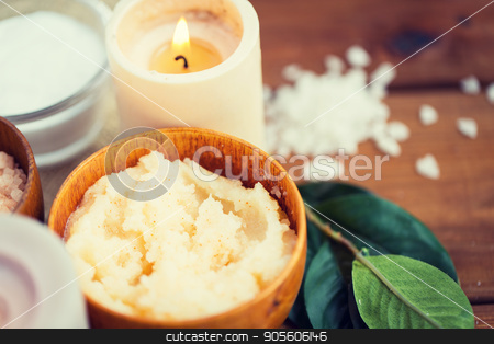 close up of natural body scrub and candle on wood stock photo, beauty, spa, therapy, natural cosmetics and wellness concept - close up of body scrub and candle on wood by Syda Productions