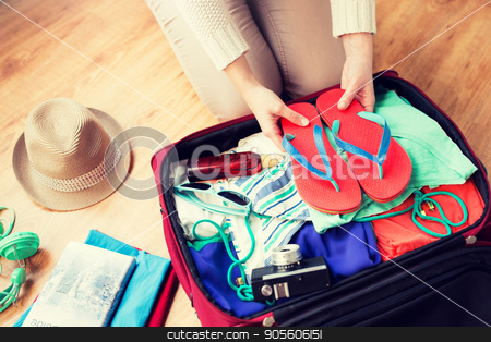 close up of woman packing travel bag for vacation stock photo, summer vacation, travel, tourism and objects concept - close up of woman packing travel bag for vacation by Syda Productions