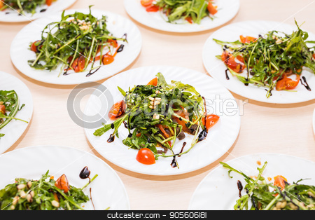Many plates with fresh salad with chicken, tomatoes, nuts and mixed greens arugula, mesclun, mache on the table. Healthy food stock photo, Fresh salad with chicken, tomatoes and mixed greens arugula, mesclun, mache on the table. Healthy food by Satura86