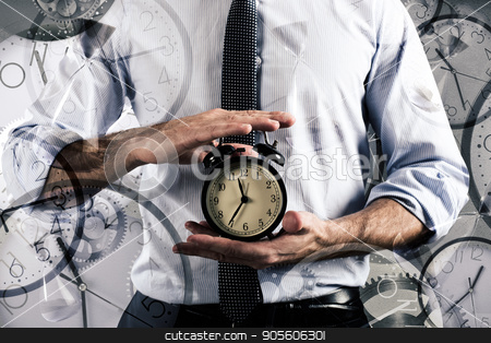 Concept of delay and time with clock stock photo, Businessman holds an alarm clock. Concept of delay and time by Federico Caputo
